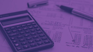Uma calculadora, uma caneta e papel com alguns dados finaceniros